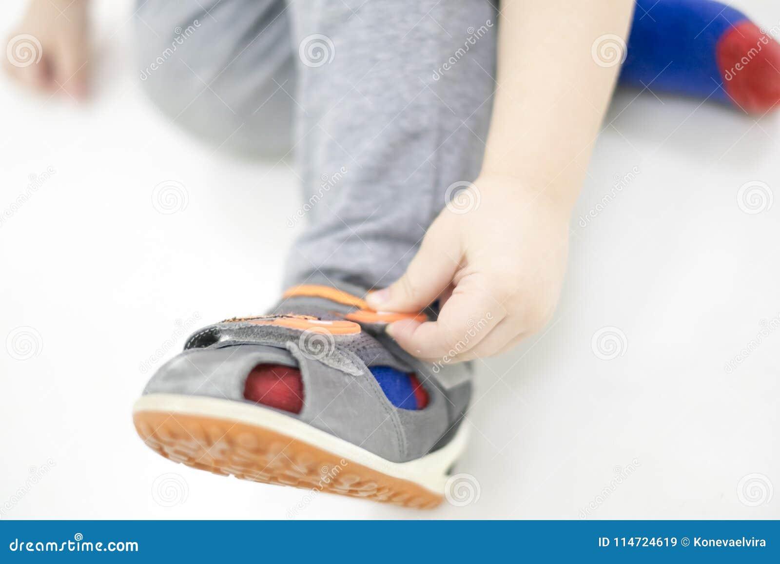 7cfbed8f6cfac Le petit enfant essaye de mettre en fonction ses chaussures Bébé garçon  avec des chaussures à