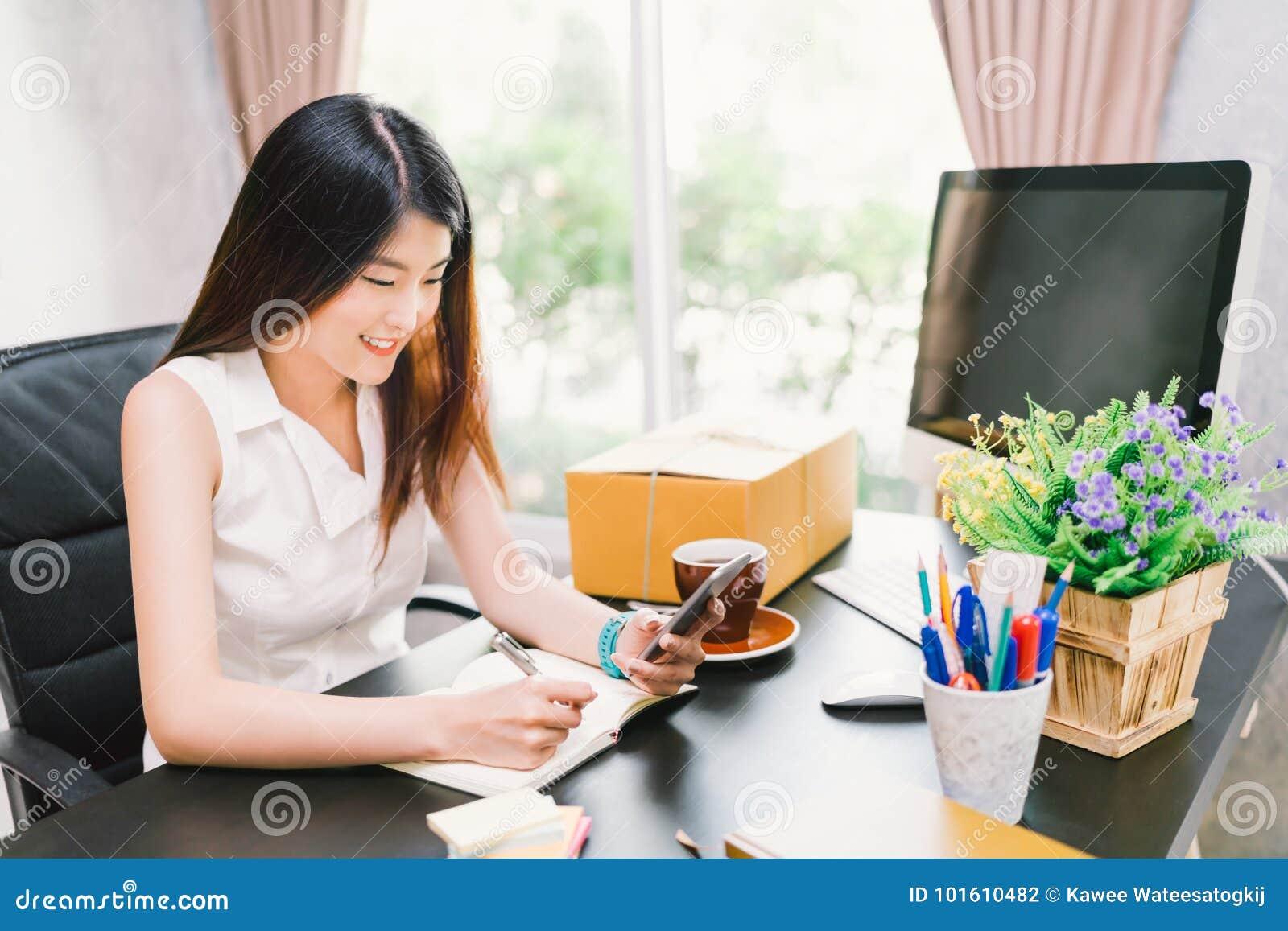 Le petit entrepreneur asiatique travaillent à la maison le bureau, utilisant l appel téléphonique de téléphone portable, écrivant