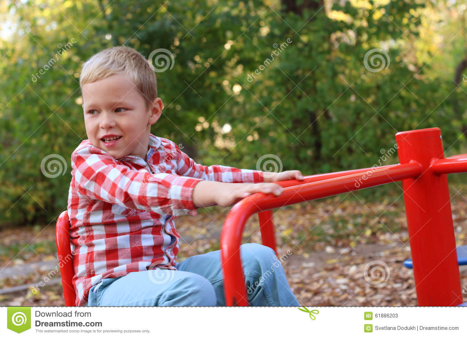 Le petit garçon beau dans la chemise joue sur le petit carrousel