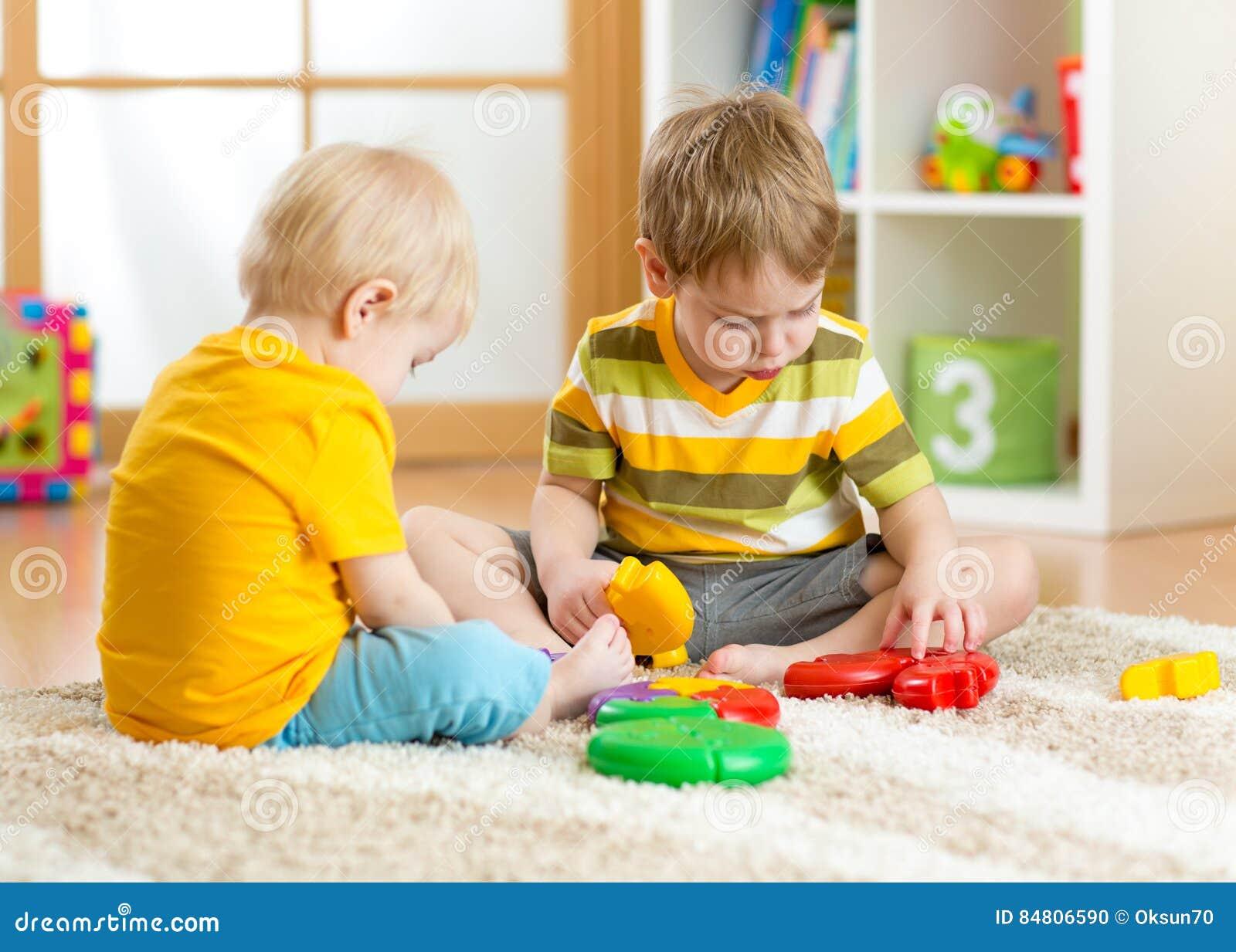 Le petit garçon d enfants joue avec un puzzle coloré multi dans la crèche