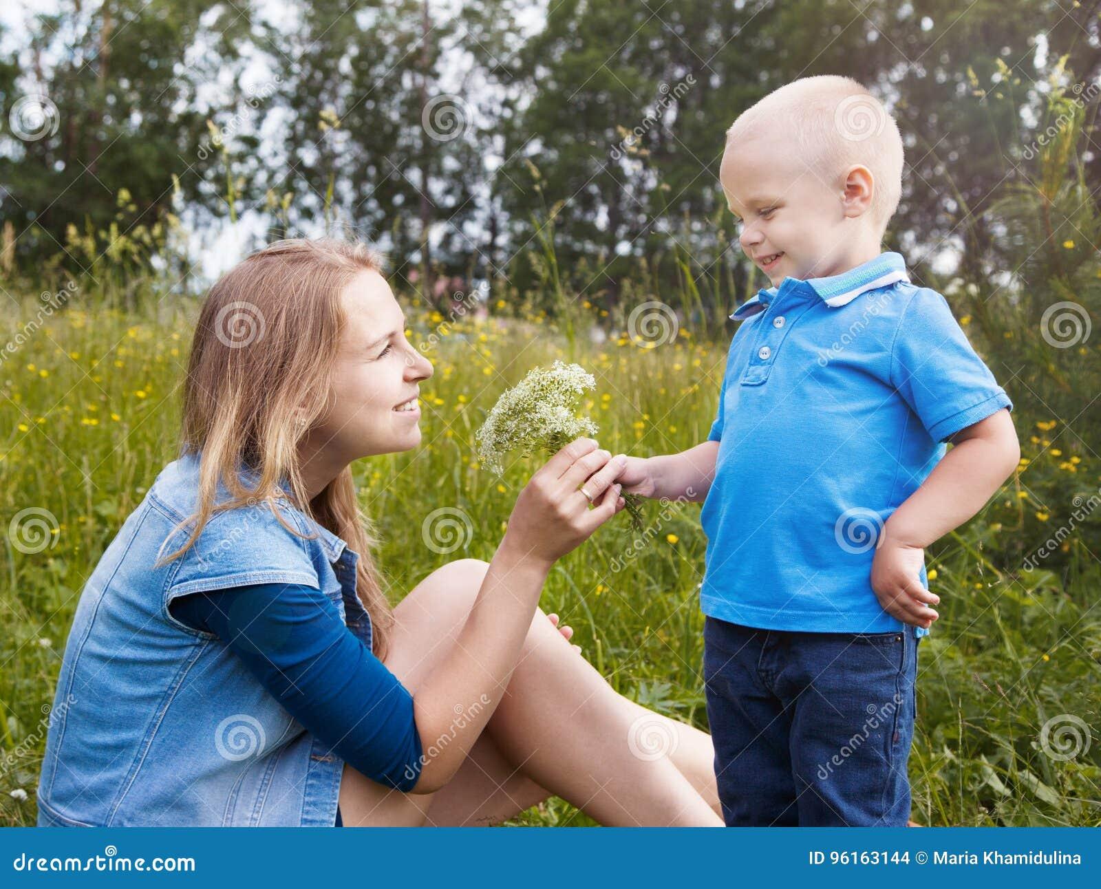 Le petit garçon donne aux fleurs sauvages de maman