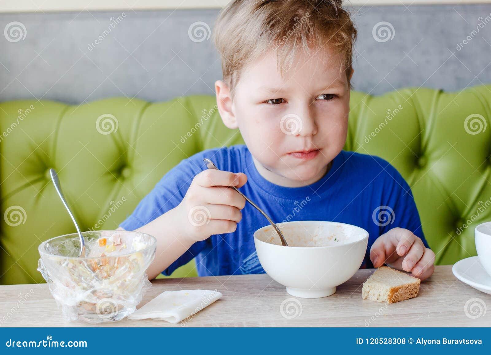 Le petit garçon est appétissant mangeant d une soupe délicieuse avec une grande cuillère