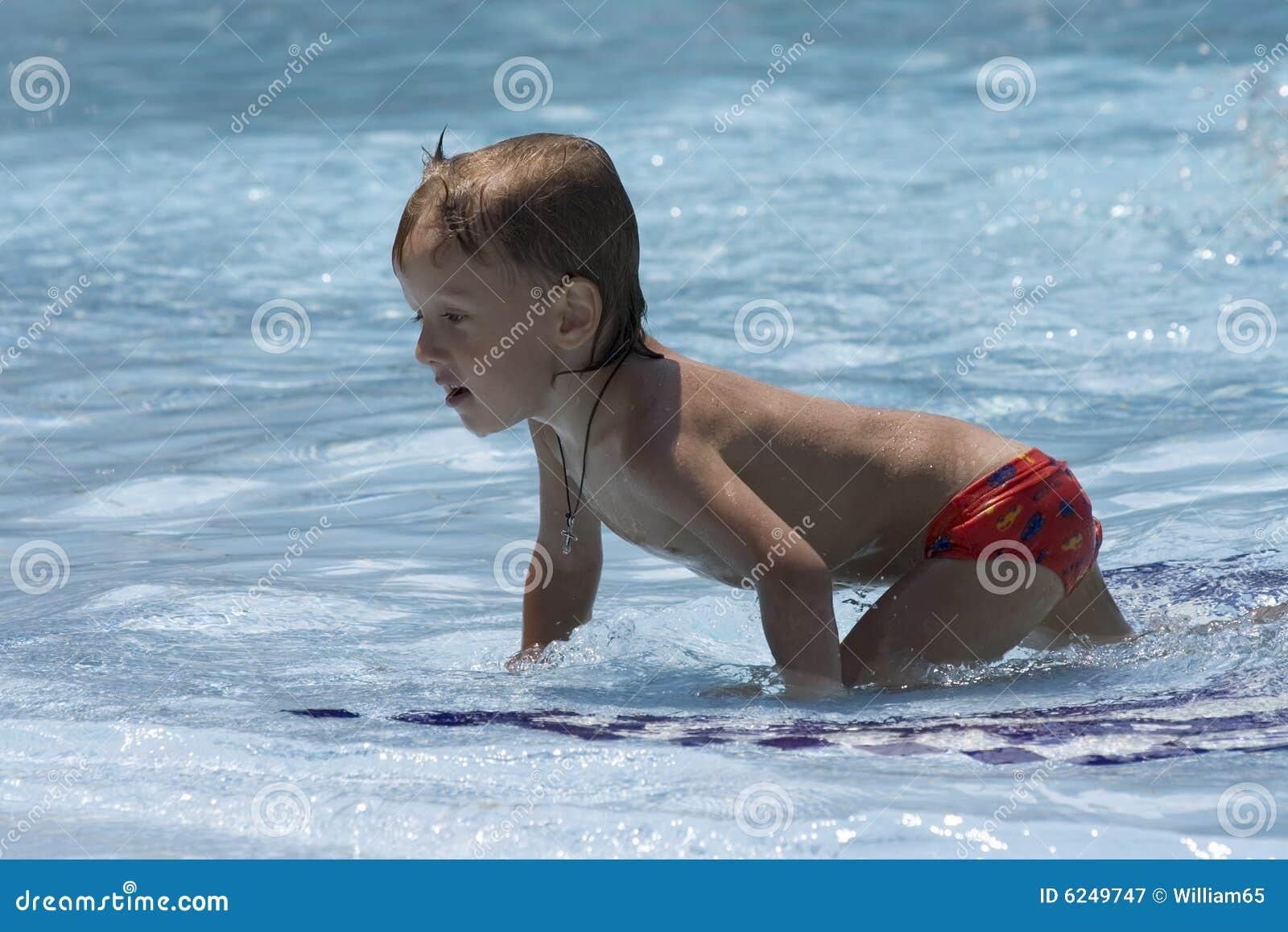 Le petit garçon humide rampe sur des genoux sur le banc