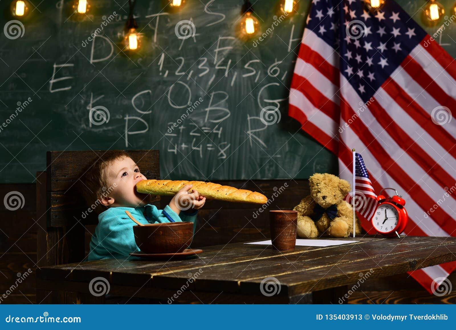 Le petit garçon mangent du pain au drapeau américain au jour de la connaissance petit garçon mangeant à la pause de midi à l écol