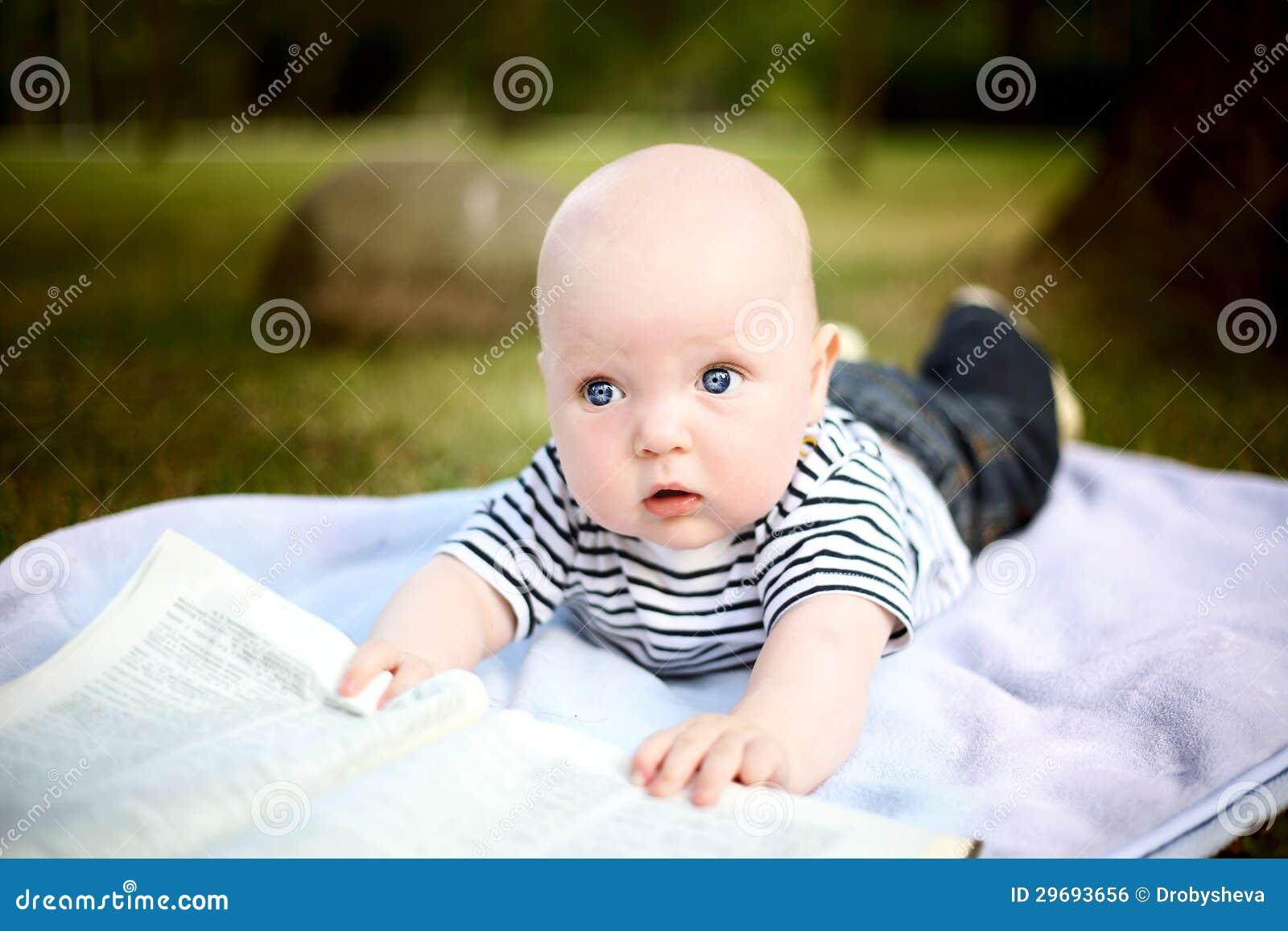 Le petit garçon mignon affiche un livre en stationnement d été