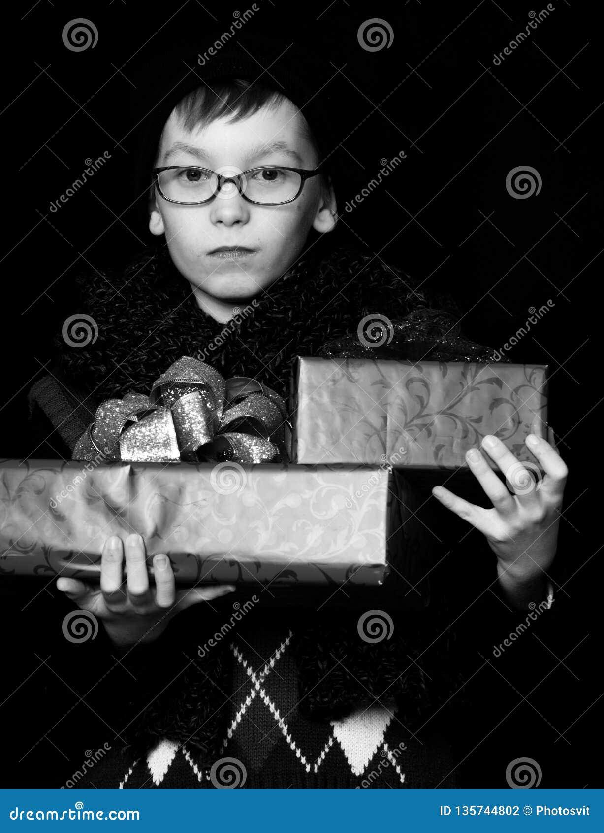 Le petit garçon ou l enfant mignon de ballot dans les verres, le chapeau et l écharpe tricotée à la mode sur le fond noir tient l