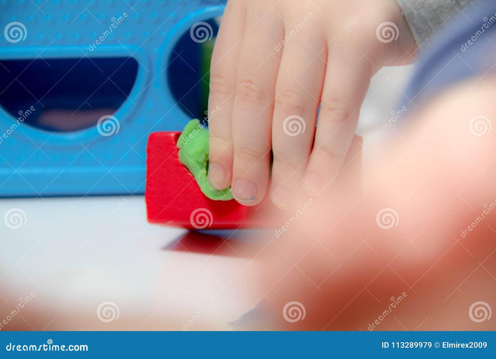 Le petit garçon trois années s assied sur la table et joue avec de la pâte à modeler et les jouets, les cubes et les matrices en