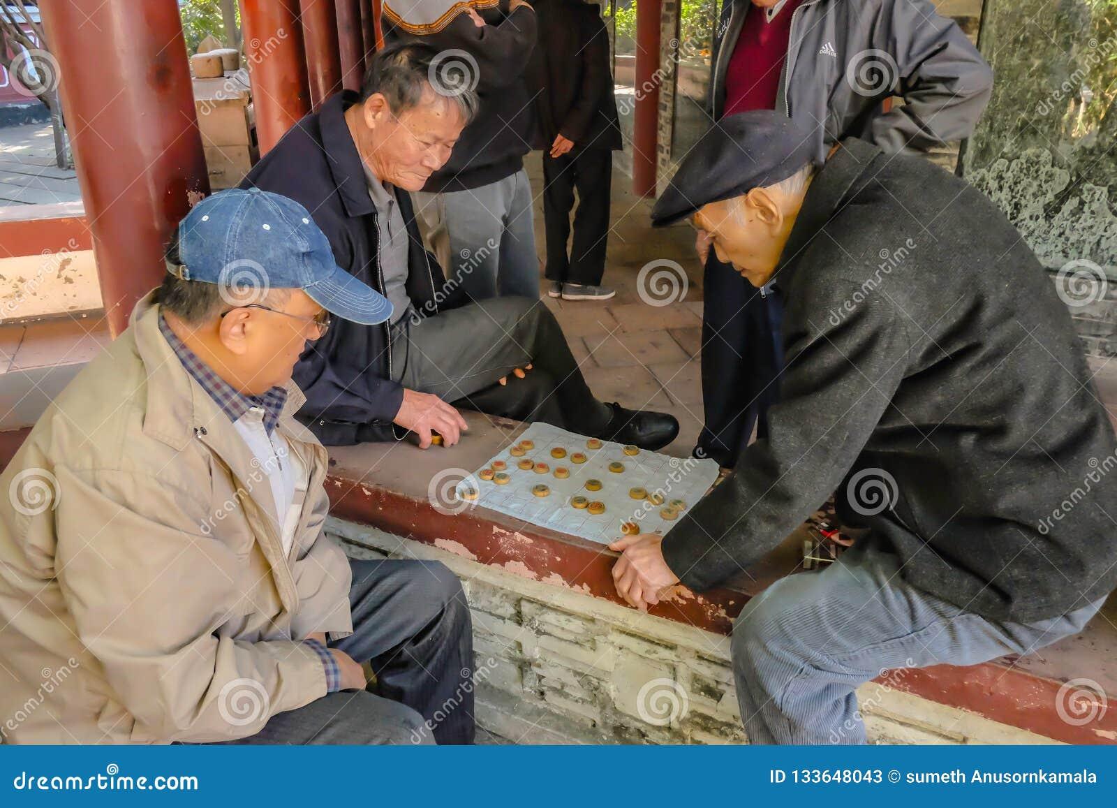 Le peuple chinois supérieur a laissé détend et jouant aux échecs chinois en parc héréditaire de temple Porcelaine de ville de Fos
