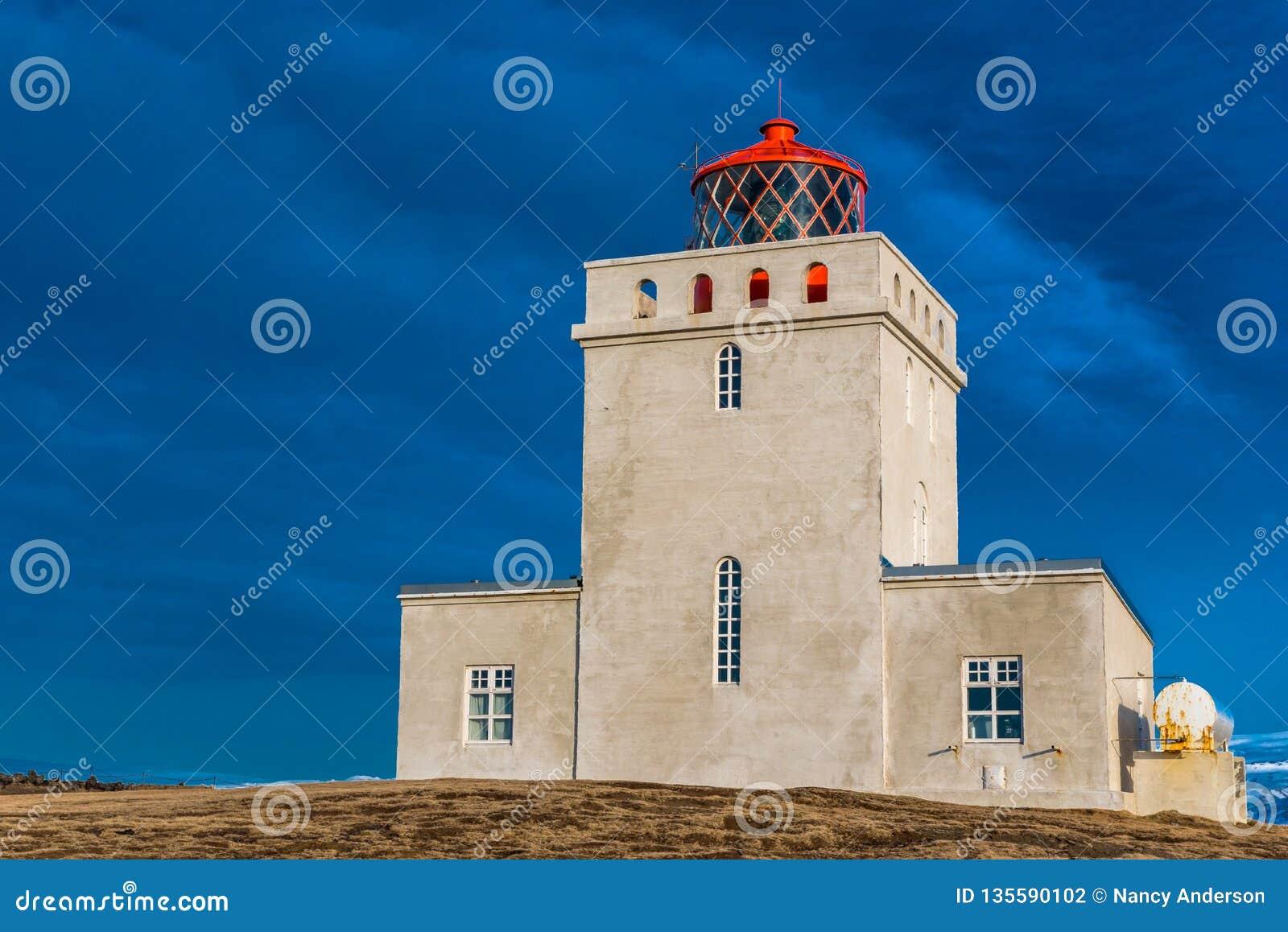 Le phare de Dyrholaey dans des supports de l Islande gardent en cieux orageux
