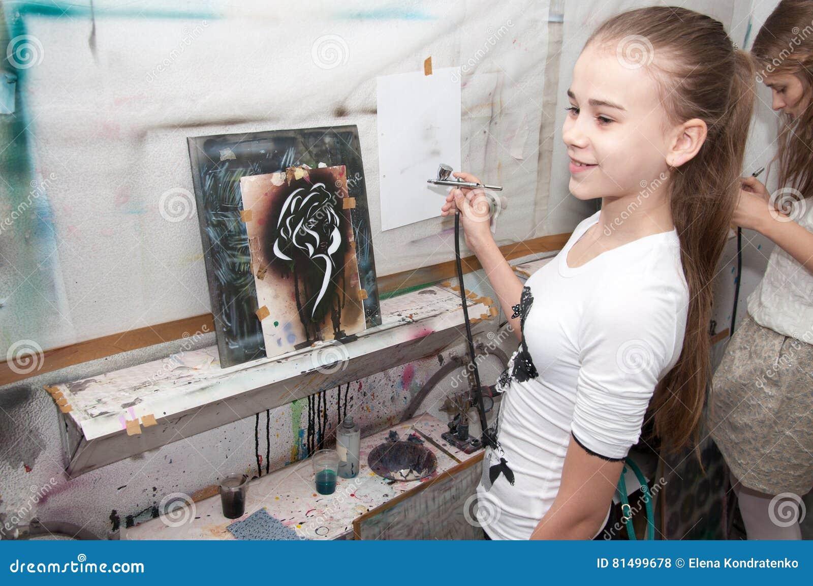 Le pitture dell adolescente della ragazza con un aerografo hanno colorato brillantemente 24 gennaio 2016 le immagini in uno studi
