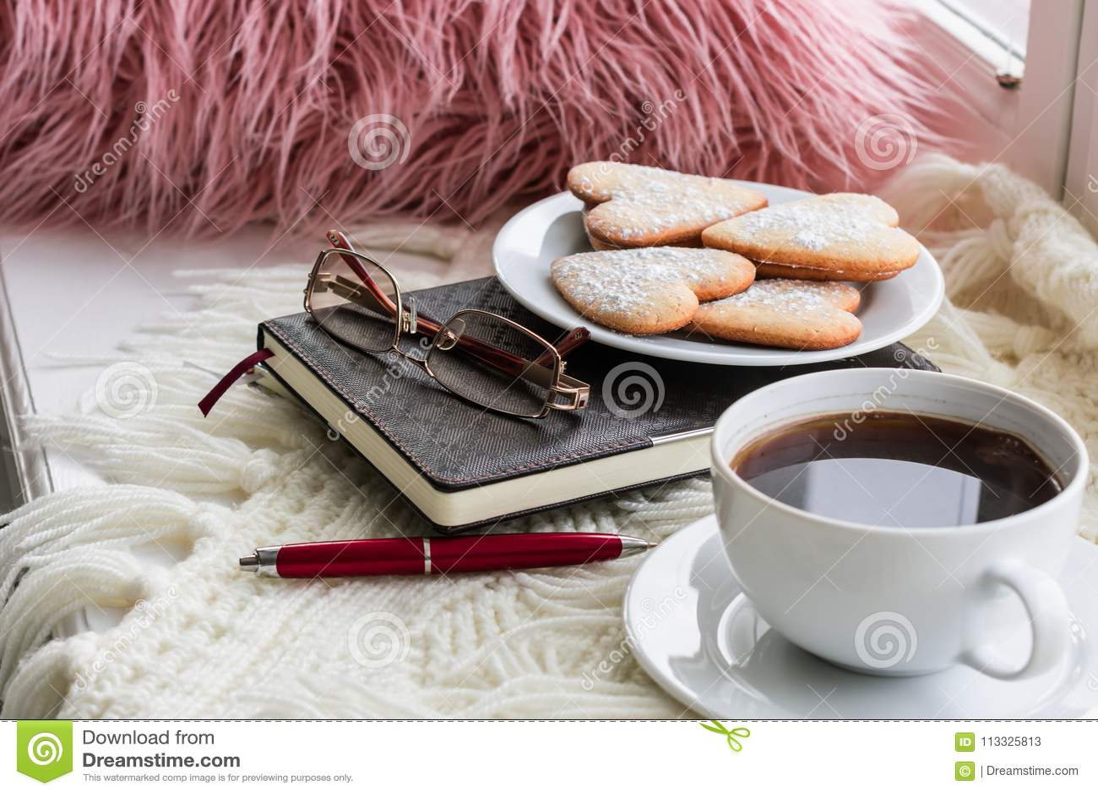 Le plaid, oreillers, livres, biscuits se trouvent sur la fenêtre