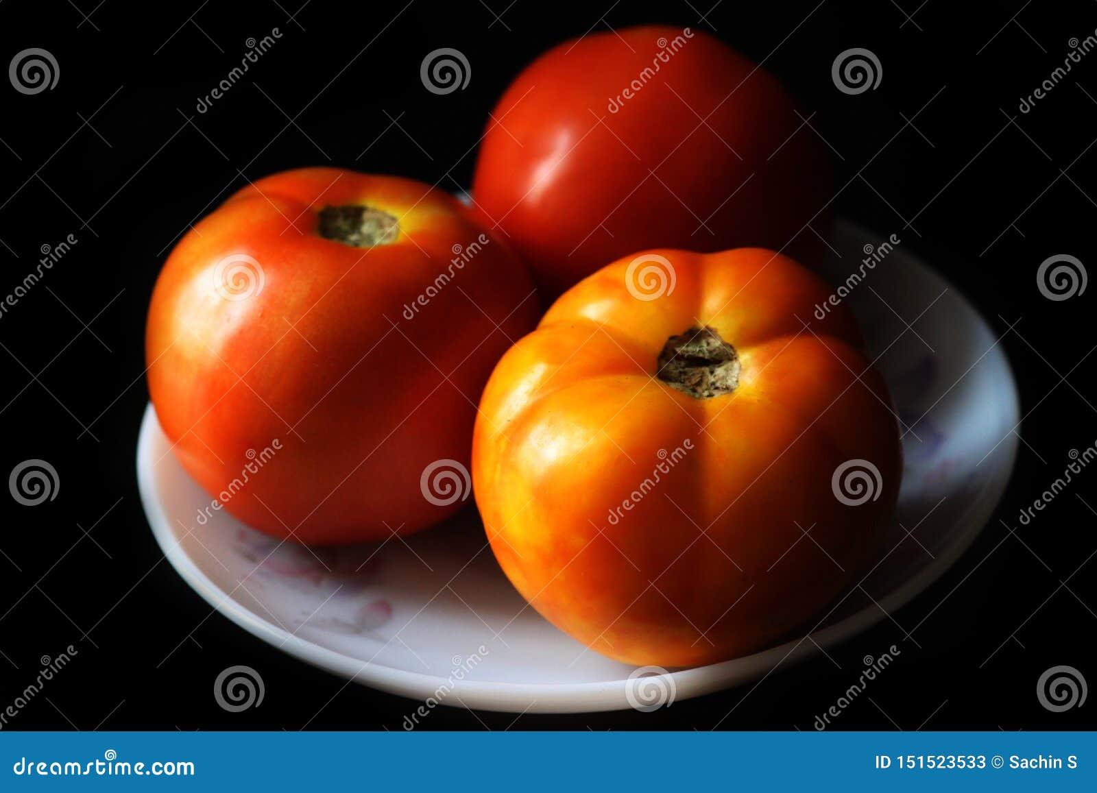 Le plan rapproché du rond frais a formé les tomates rouges organiques