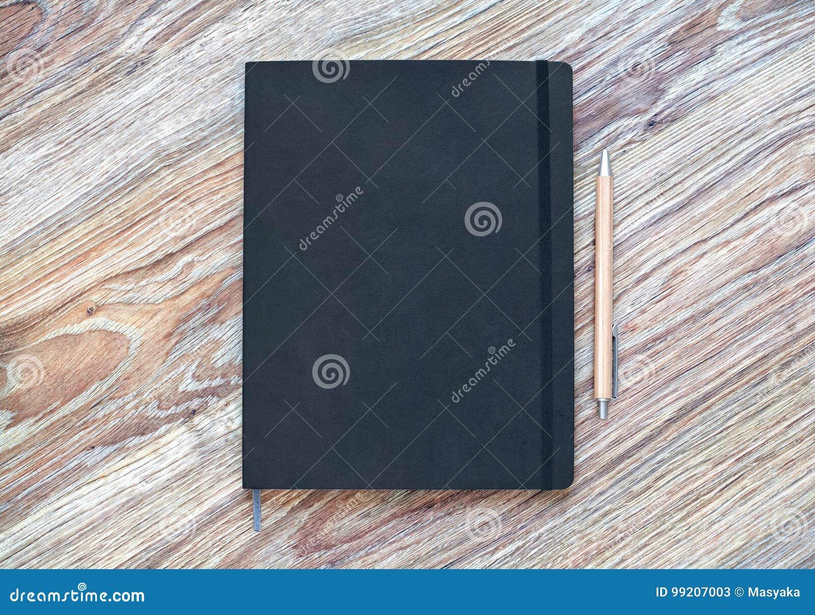 Le planificateur fermé avec le stylo est sur un bureau en bois