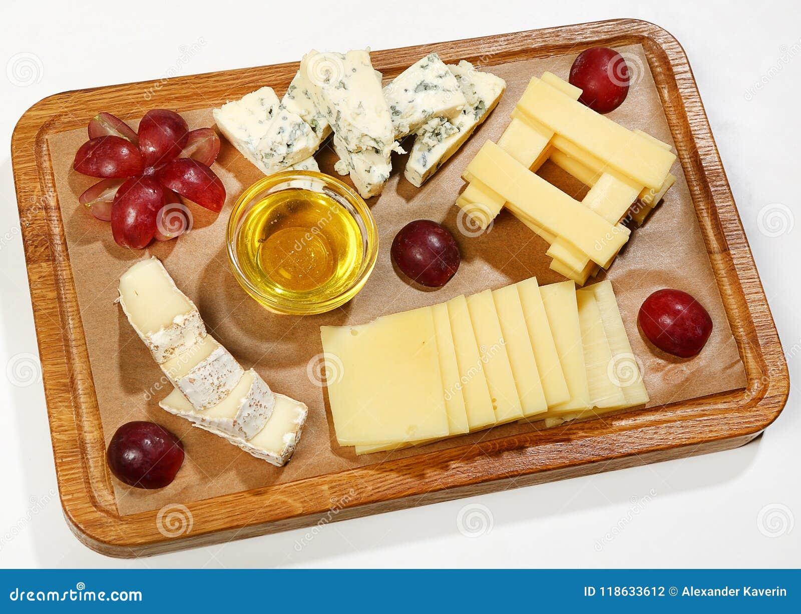 Le plat de fromage - camembert, fromage de Dorblu, parmesan, cheddar, Néerlandais, a servi avec des raisins, le miel et des noix