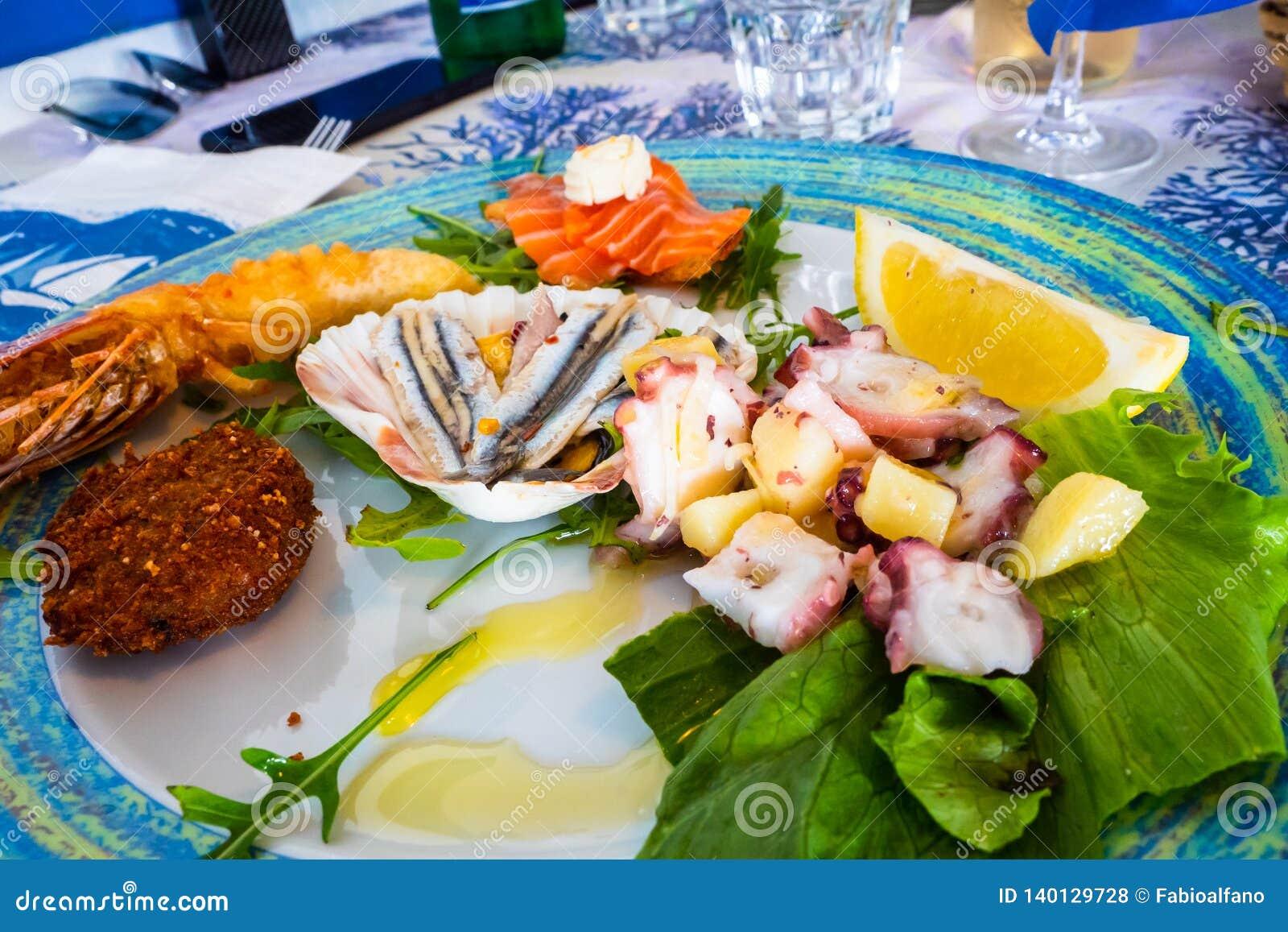 Le plat de fruits de mer a mélangé des poissons, salade de poulpe, crevette rouge frite, anchois assaisonné avec l huile d olive