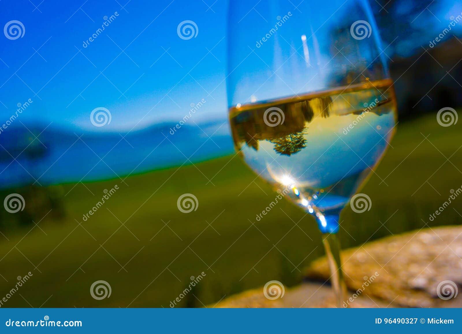 Le plein verre de vin blanc reflète le terrain de golf