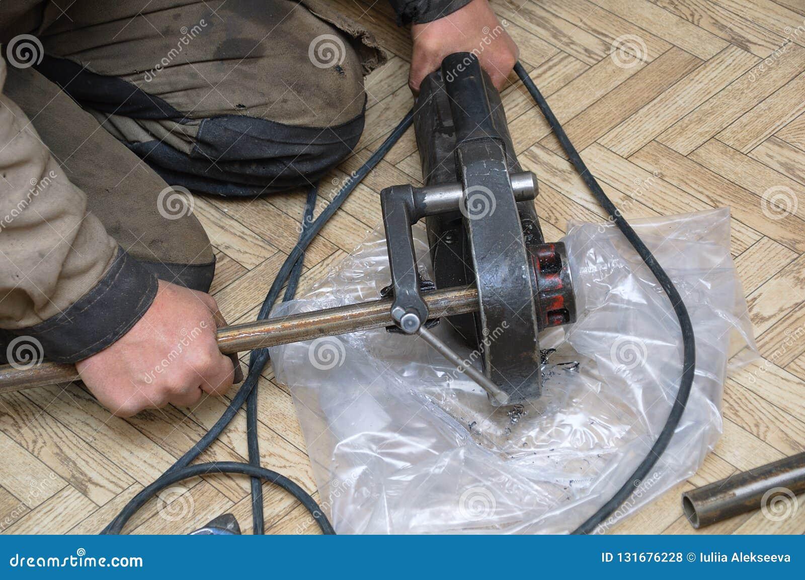 Le plombier serre le tube en métal de la presse avec des coutils