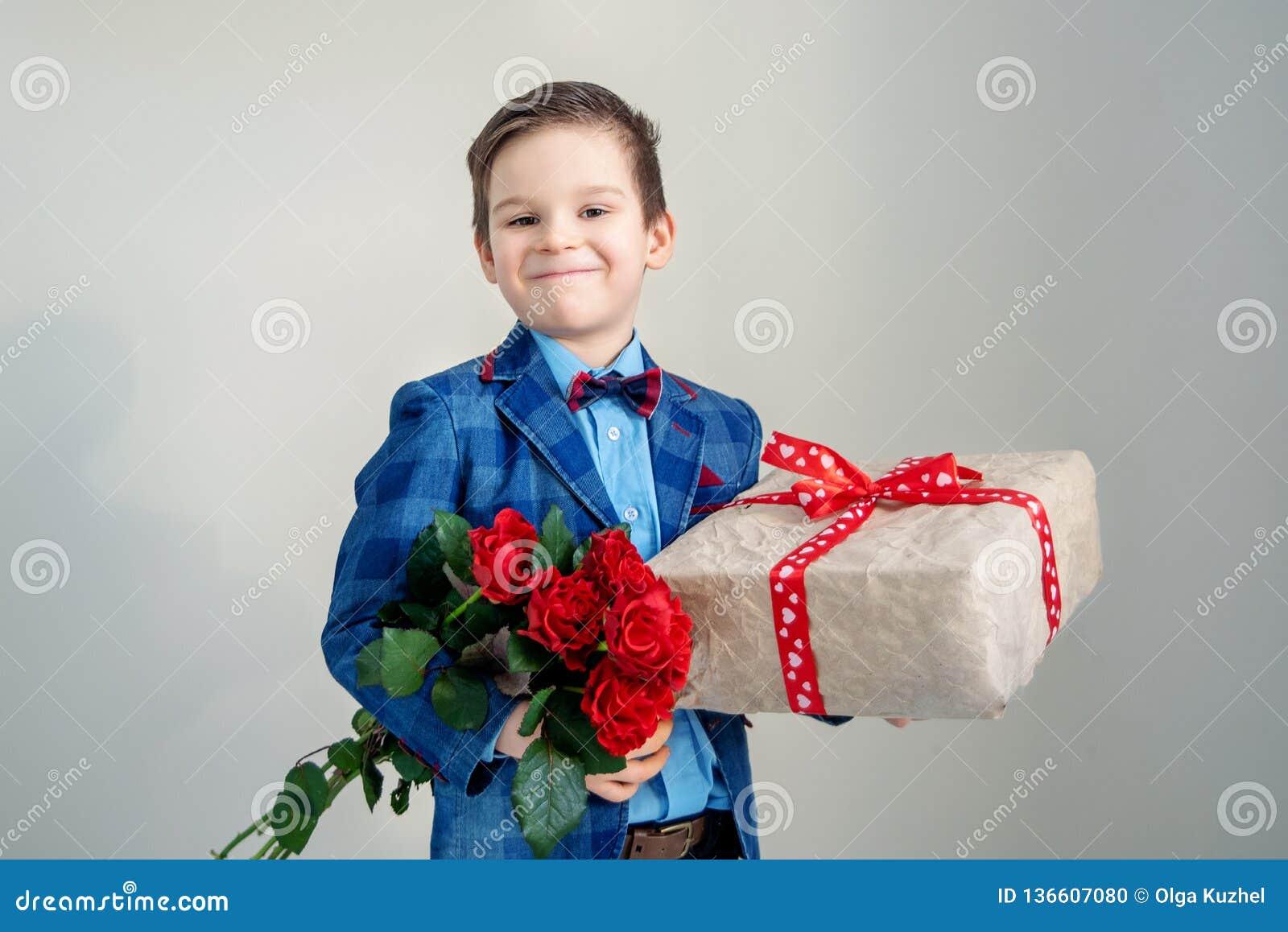Le pojken med buketten av blommor och en gåva på en ljus bakgrund