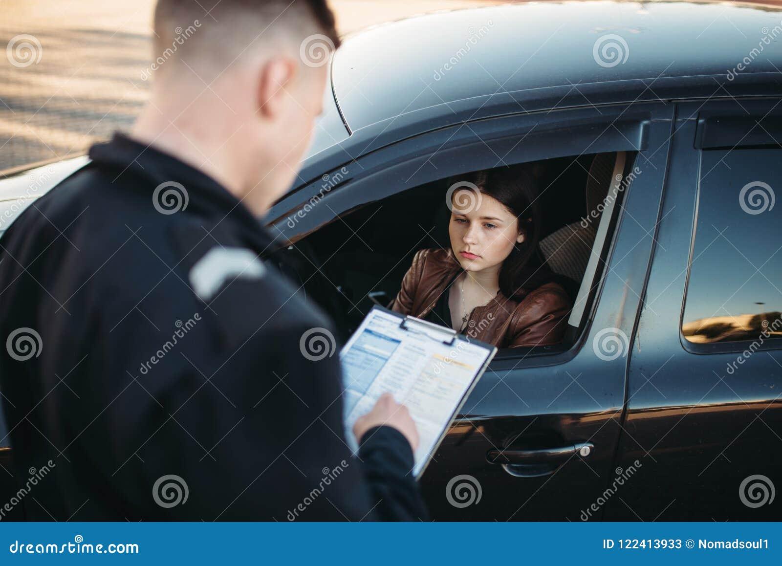 Le policier dans l uniforme écrit très bien au conducteur femelle