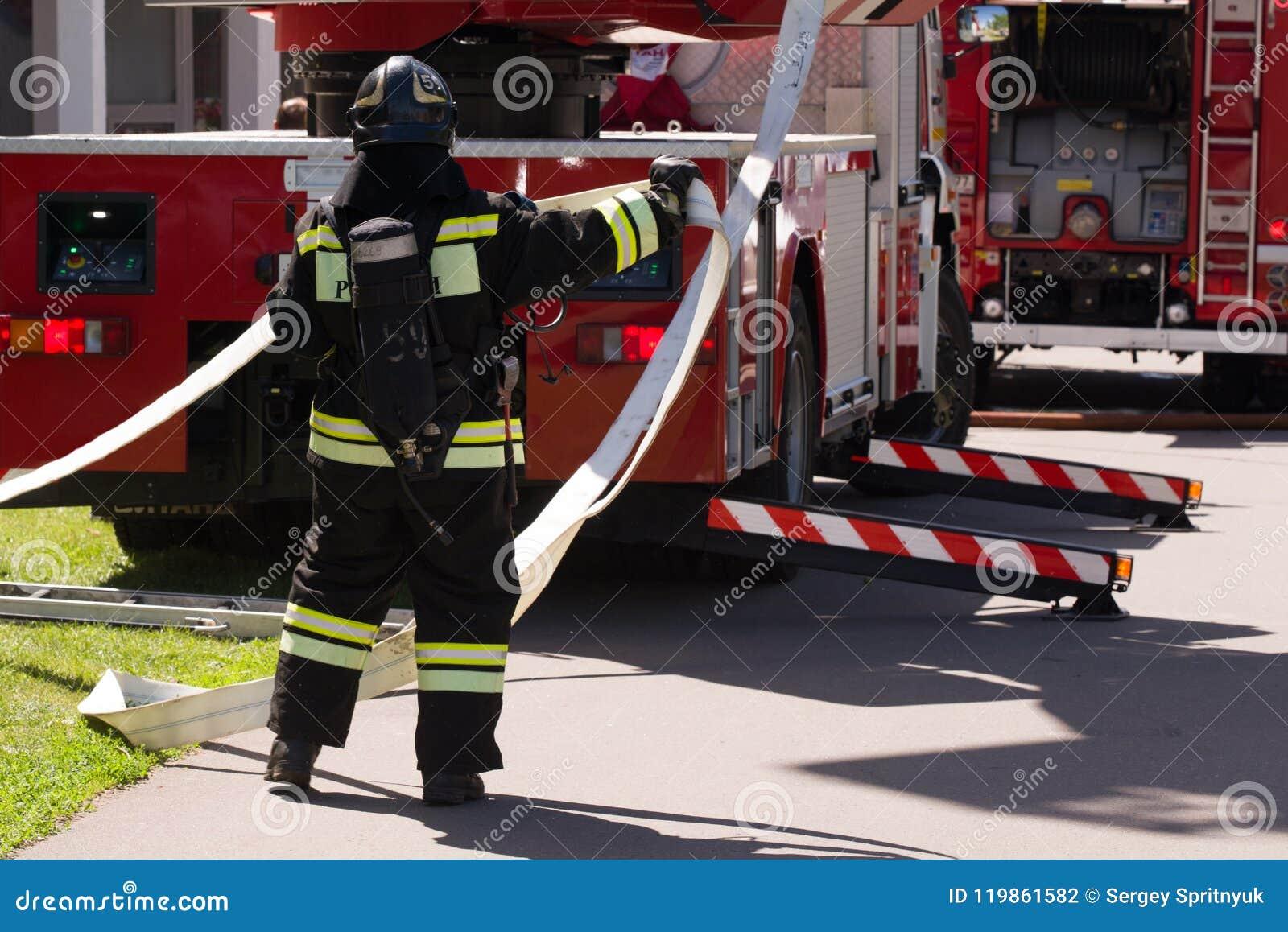 Le pompier déroule la bouche d incendie près du camion de pompiers