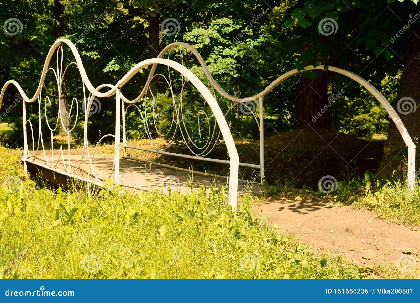 Le pont forgé blanc dans un jardin