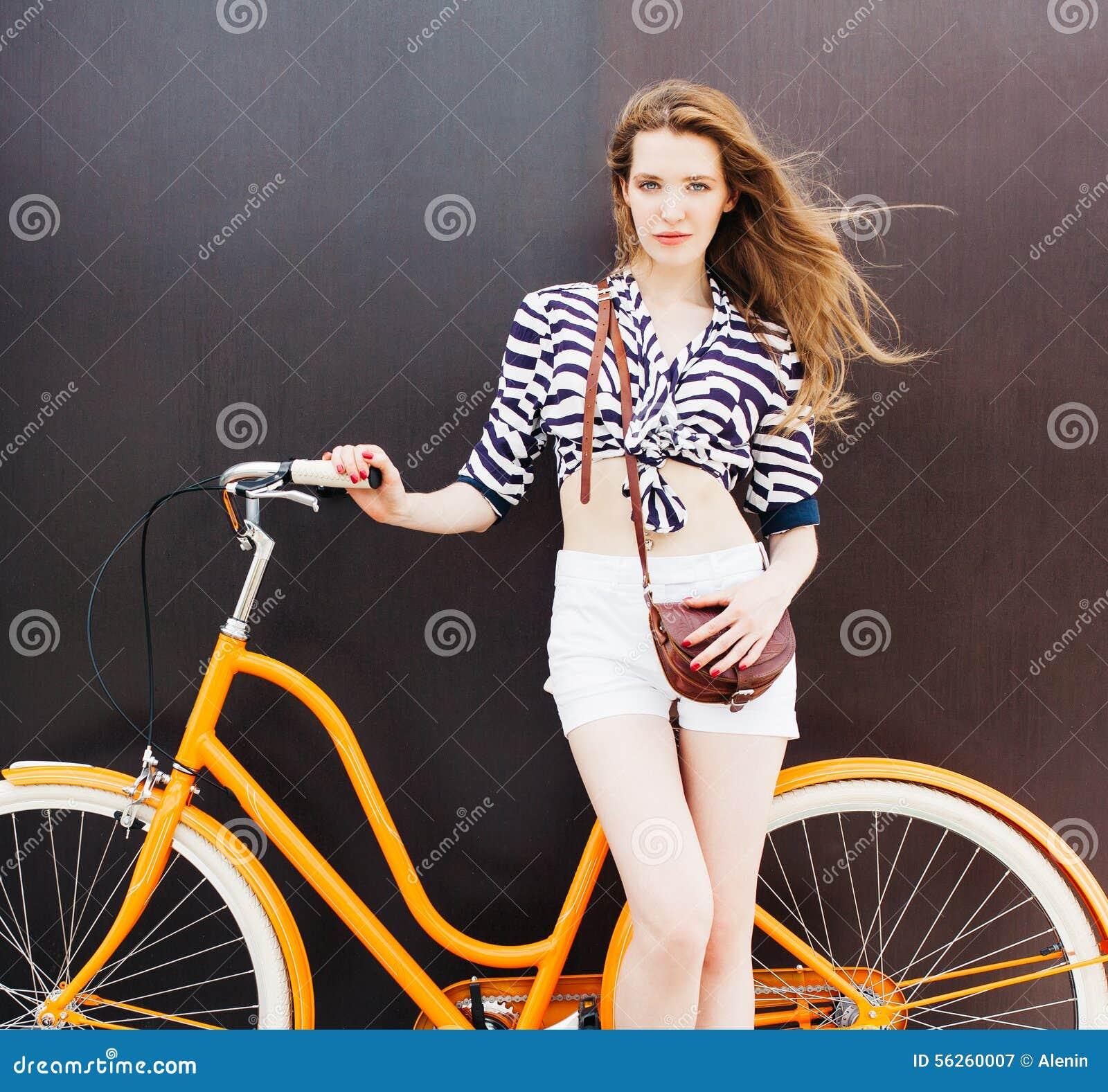 Le portrait d été de la belle jeune femme se tient à la bicyclette de vintage Le vent souffle ses cheveux Fond foncé Couleurs cha