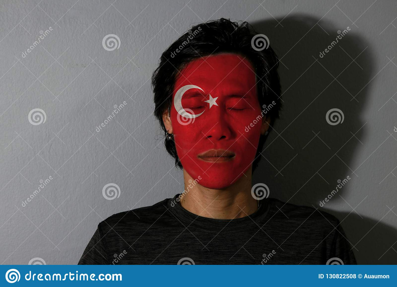 Le portrait d un homme avec le drapeau de la Turquie a peint sur son visage et yeux étroits avec l ombre noire sur le fond gris