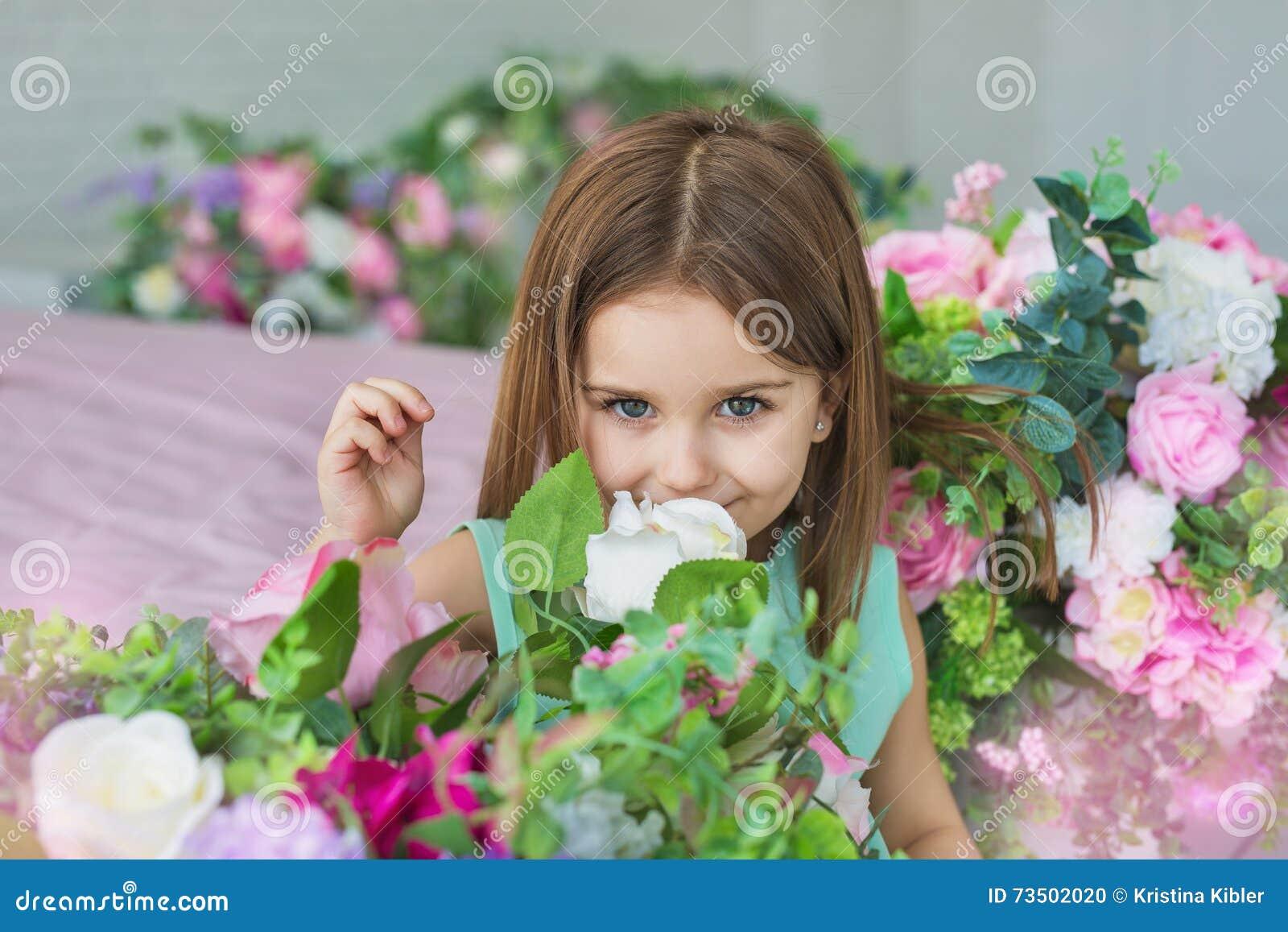 Le portrait d une fille assez petite dans une robe de turquoise renifle des fleurs dans un studio