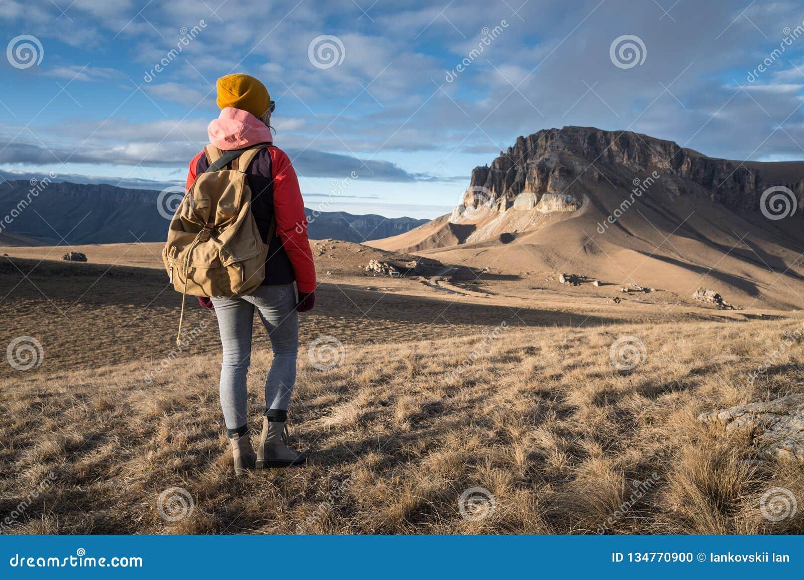 Le portrait de derrière d une voyageuse de fille dans une veste avec une capsule et un sac à dos se tient sur le fond d une épopé
