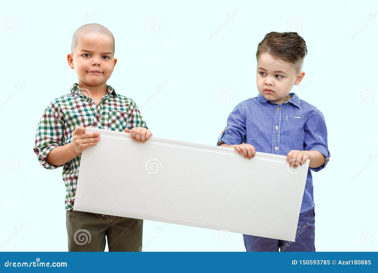 Le portrait de deux garçons tenant le blanc se connectent le fond d isolement