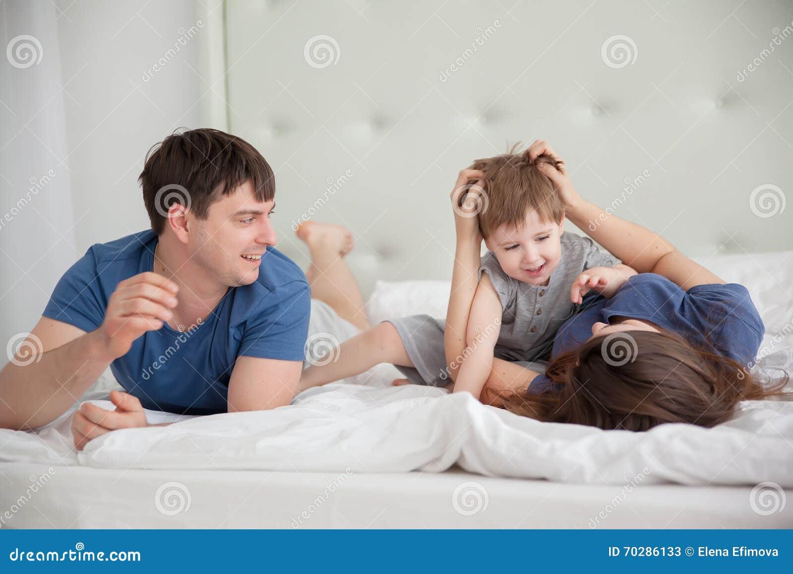 Le portrait de famille de trois personnes sur des parents enfoncent les pyjamas de port
