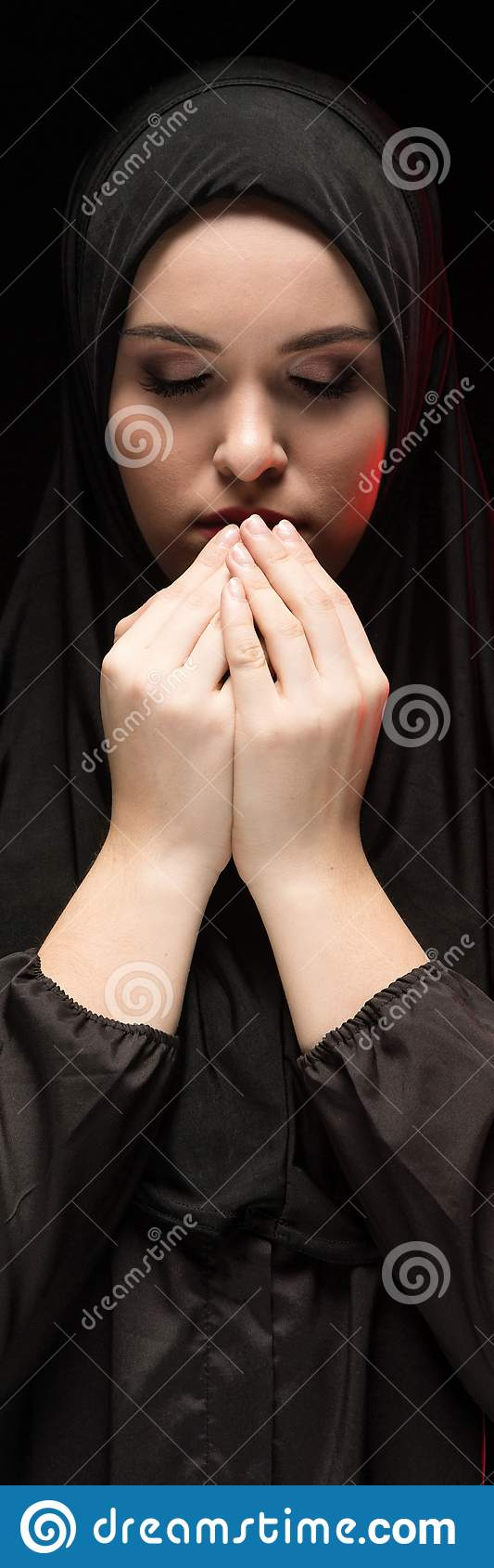 Le portrait de la belle jeune femme musulmane sérieuse portant le hijab noir avec des mains s approchent de son visage en tant qu