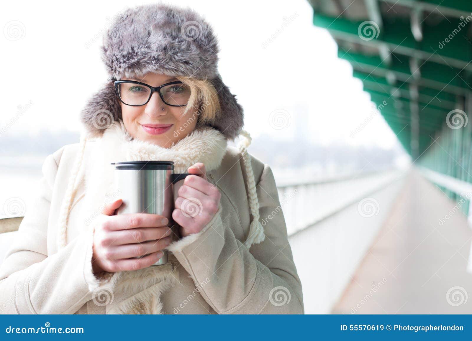 Le portrait de la femme de sourire dans la participation chaude d habillement a isolé le récipient de boissons