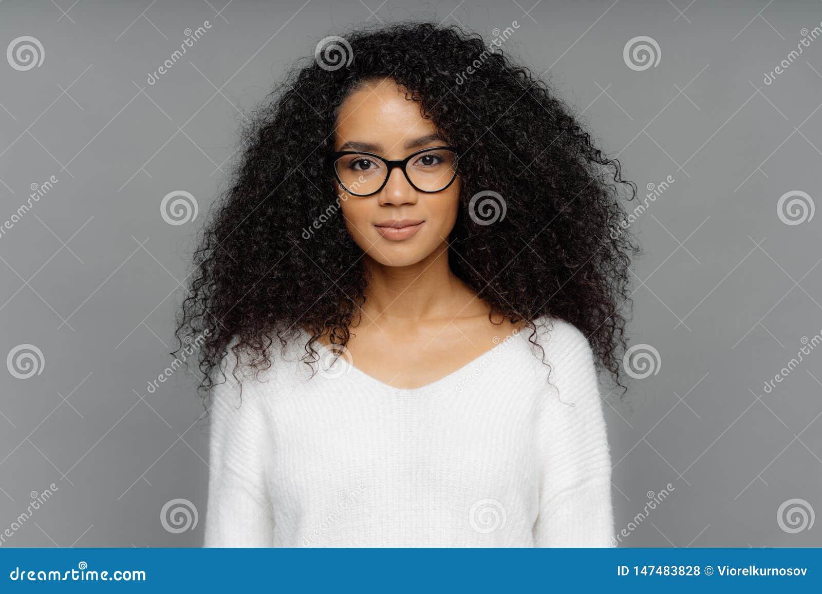 Le portrait de la femme sérieuse avec la peau foncée, cheveux touffus d Afro, porte de grandes lunettes transparentes et le chand