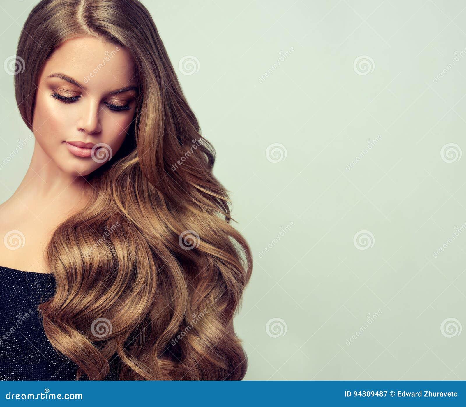 Le portrait de la jeune femme magnifique avec élégant composent et coiffure parfaite
