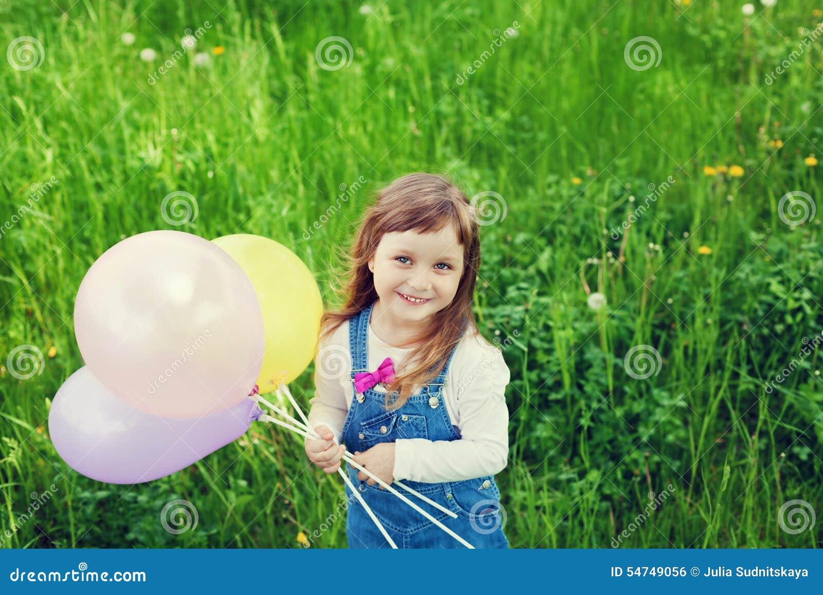 Le portrait de la petite fille mignonne avec le beau sourire tenant le jouet monte en ballon à disposition sur le pré de fleur, e