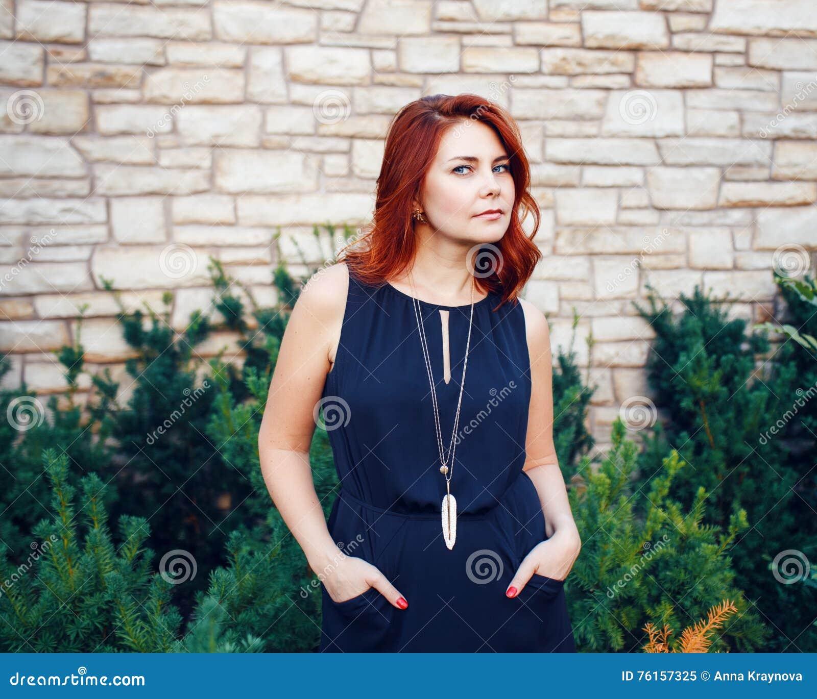 Le portrait de plan rapproché du milieu de sourire a vieilli la femme caucasienne blanche avec les cheveux rouges bouclés ondulés