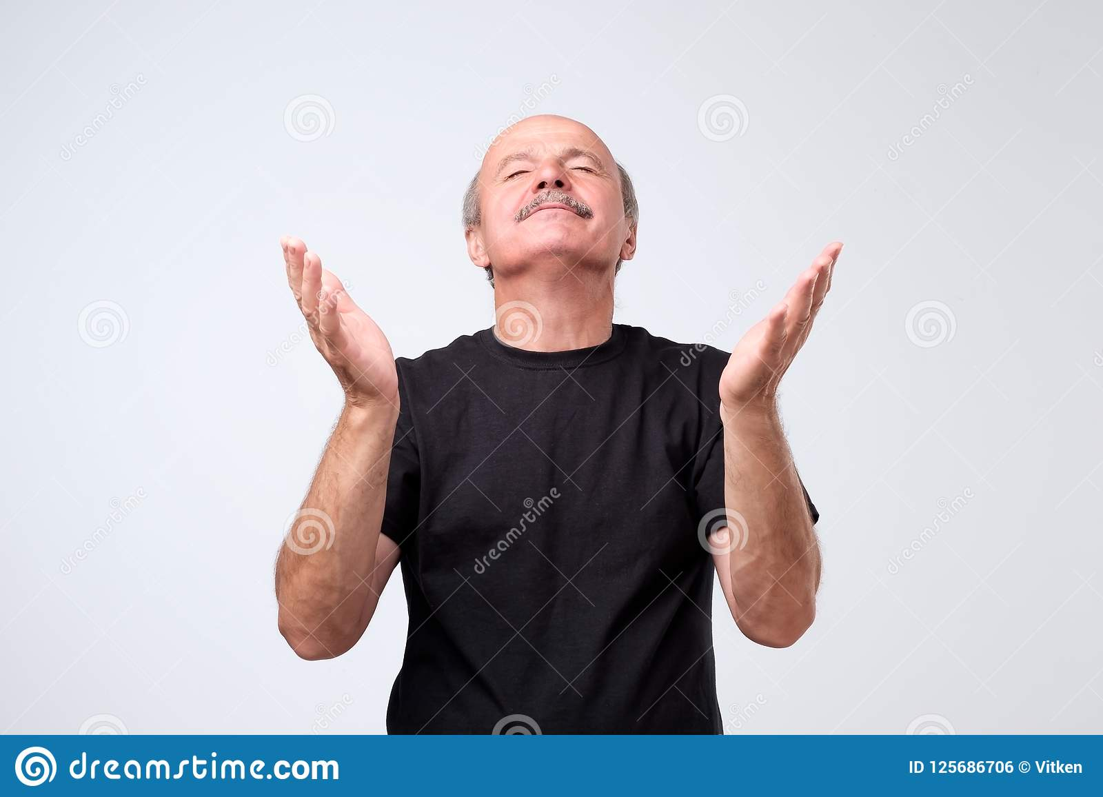 Le portrait de prier l homme caucasien dans l équipement occasionnel, tenant des mains prient dedans et recherchant si tout va bi