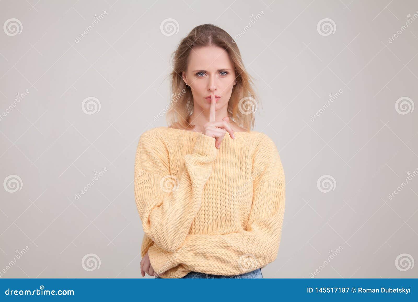 Le portrait de taille- disparaissent jeune femme blonde montrant le signe de silence avec l expression s?rieuse de visage demande