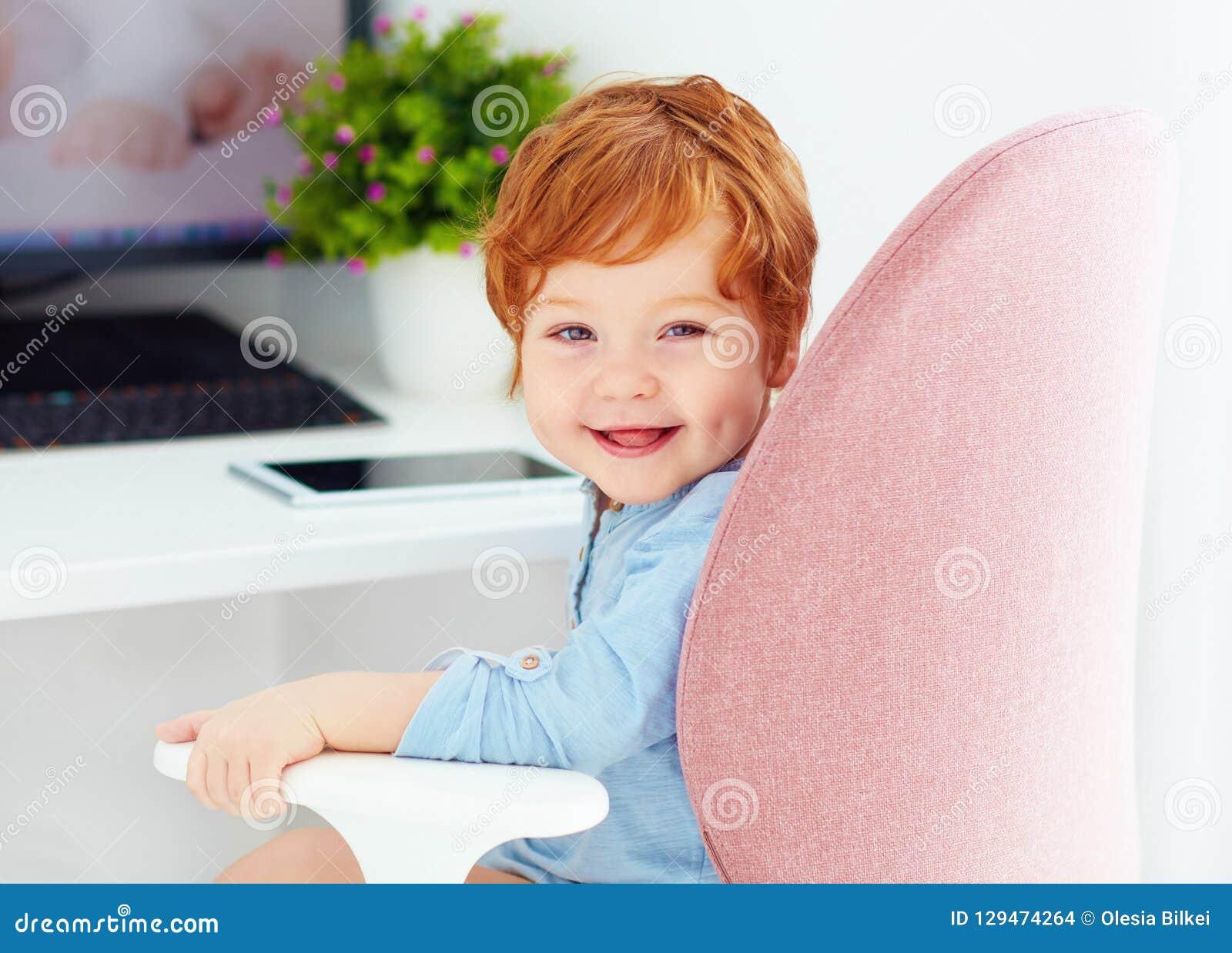 Le portrait du bébé garçon heureux d enfant en bas âge se repose dans la chaise au lieu de travail