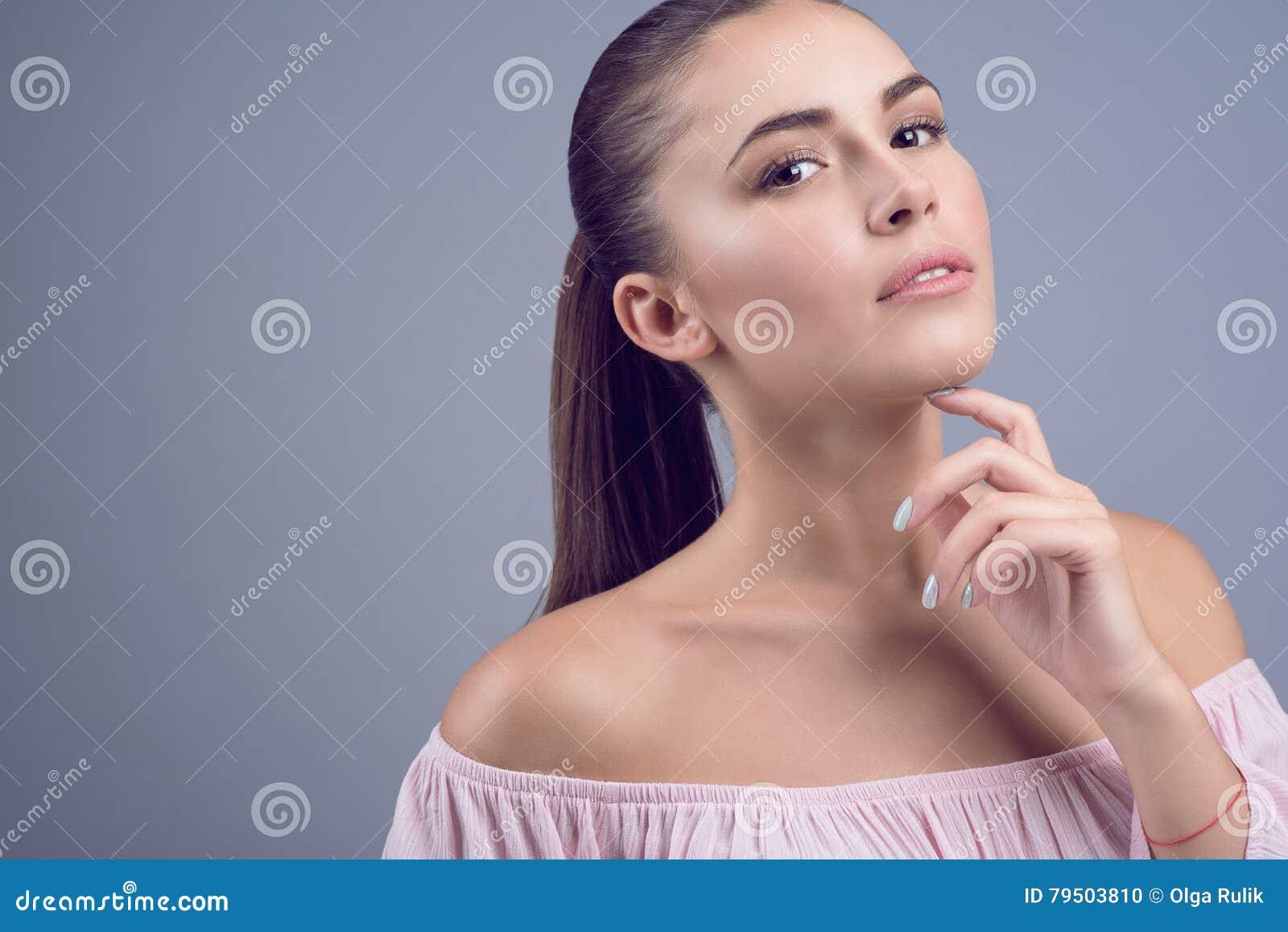 Le portrait du beau jeune modèle aux cheveux foncés avec la peau parfaite et la nudité humide composent sur le fond gris