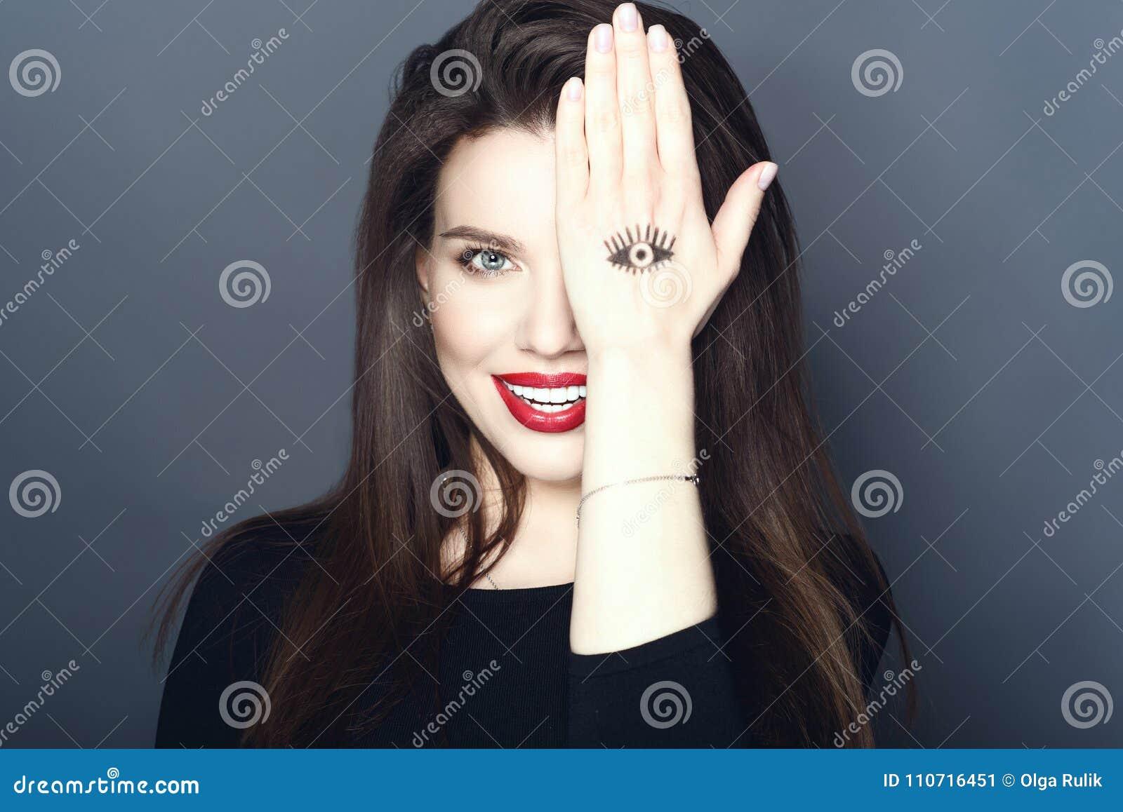 Le portrait du beau sourire composent l artiste cachant son oeil derrière la main avec l oeil dessiné là-dessus