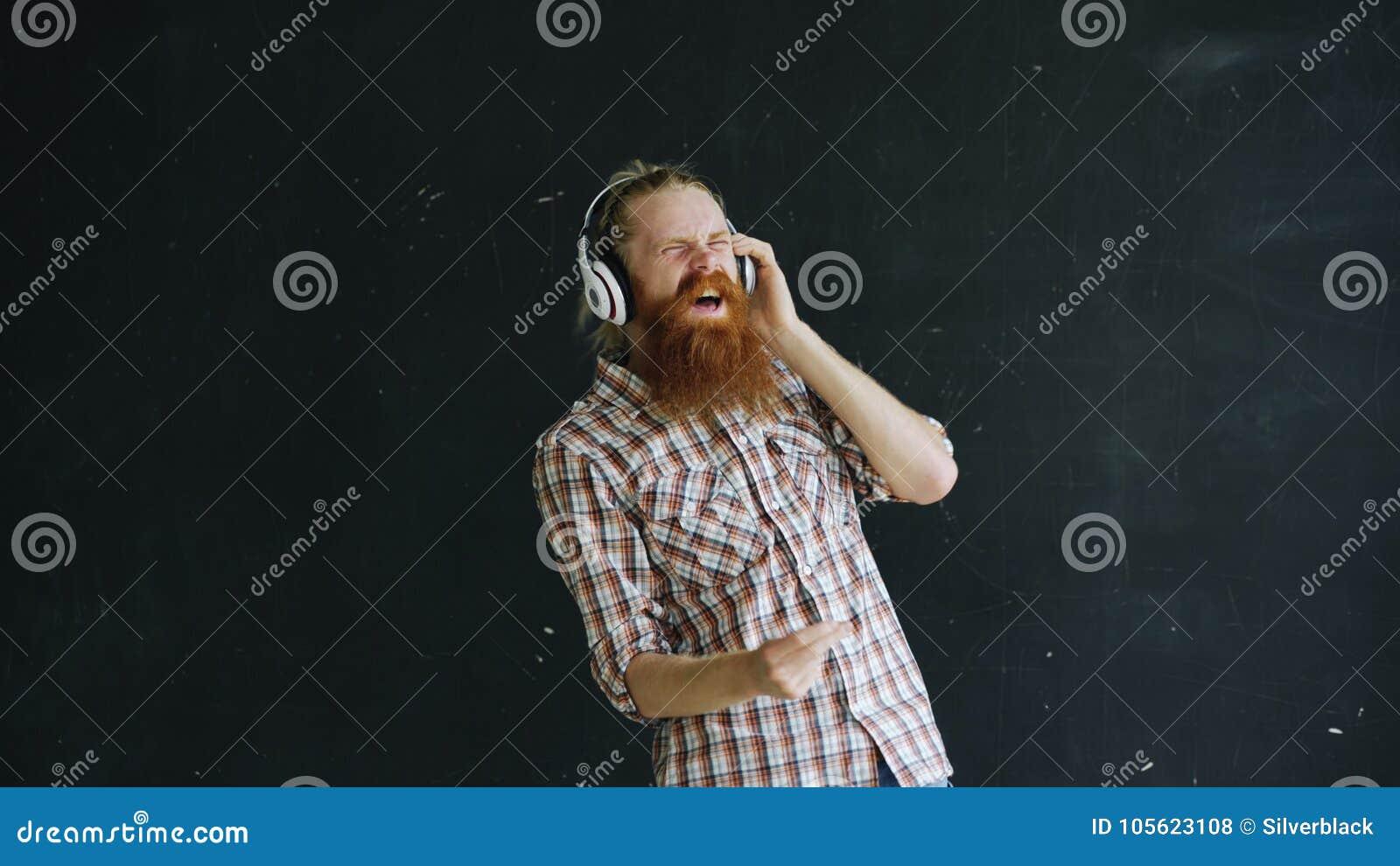 Le portrait du jeune homme barbu met dessus des écouteurs et la danse tandis qu écoutez la musique sur le fond noir
