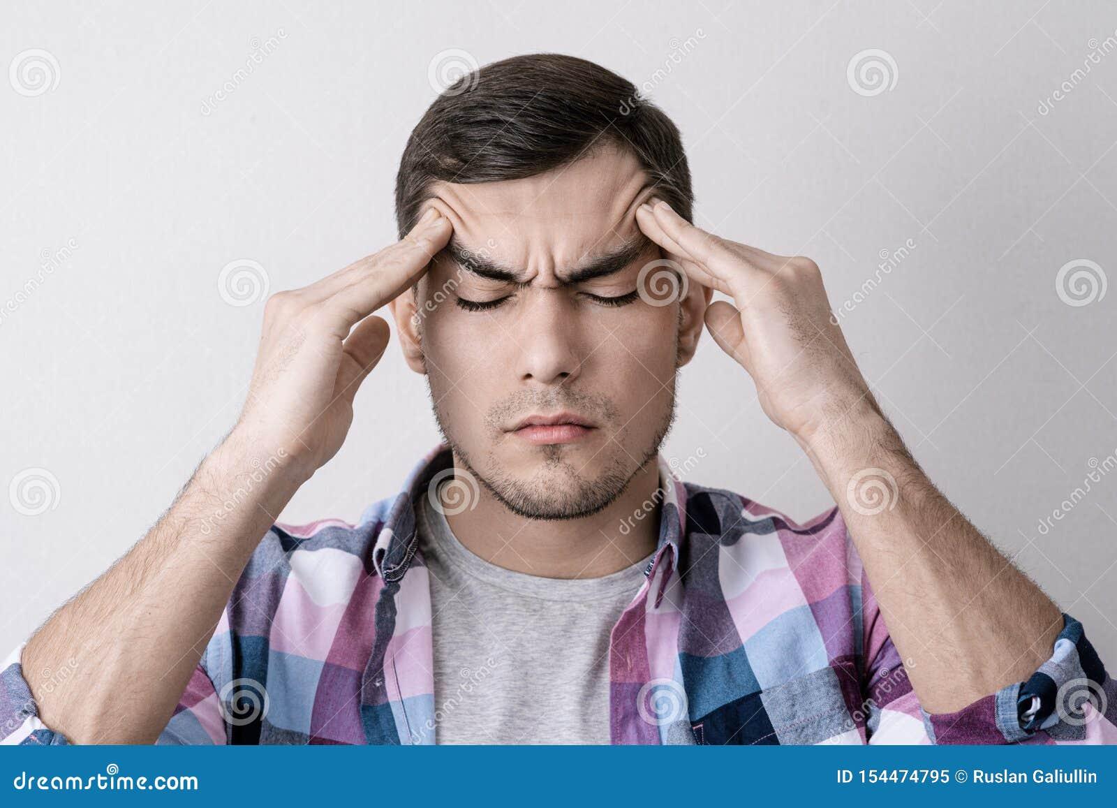 Le portrait du jeune homme caucasien avec le mal de tête, pressant ses doigts sur sa tête avec ses yeux s est fermé