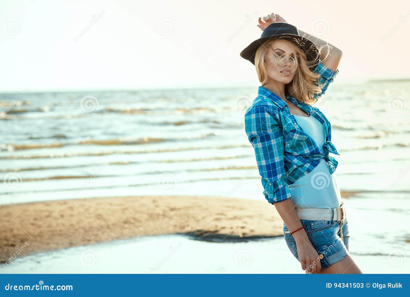 Le portrait du jeune modèle blond sexy magnifique dans le noir a senti les cheveux, la chemise bleue vérifiée et les shorts de de