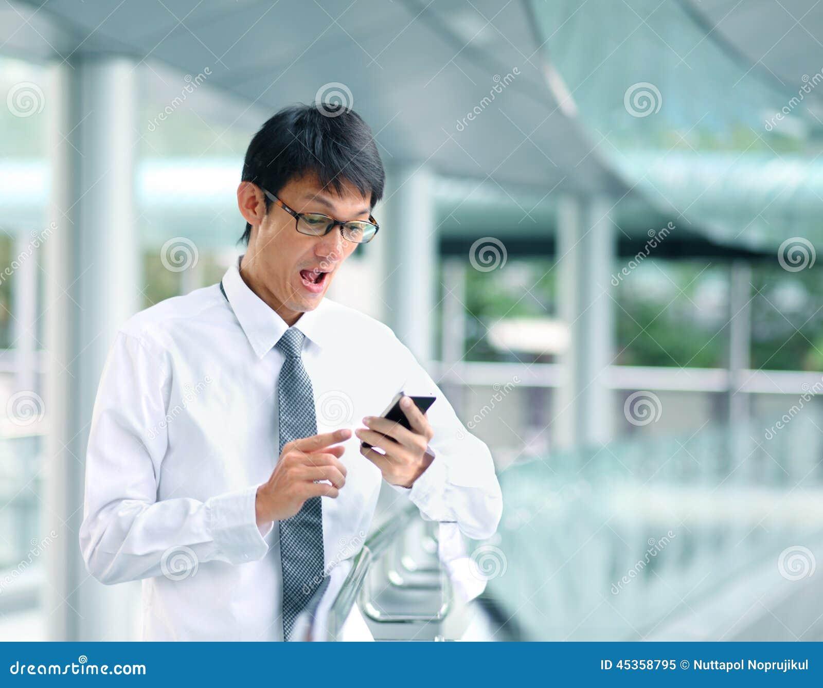 Le portrait du jeune regard d homme d affaires a effrayé avec le smartphone