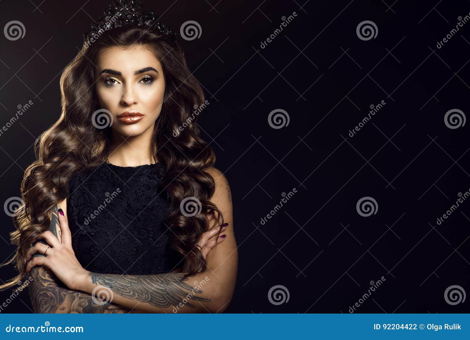 Le portrait du modèle tatoué par charme magnifique avec de longs cheveux soyeux onduleux et provocateurs composent la robe de den