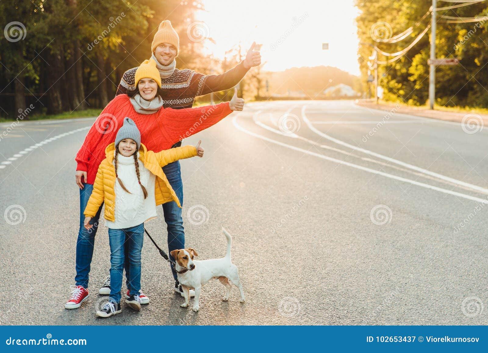 Le portrait extérieur de la jolie femme, son mari et la fille montrent le signe correct, marchent avec le chien sur la route, app
