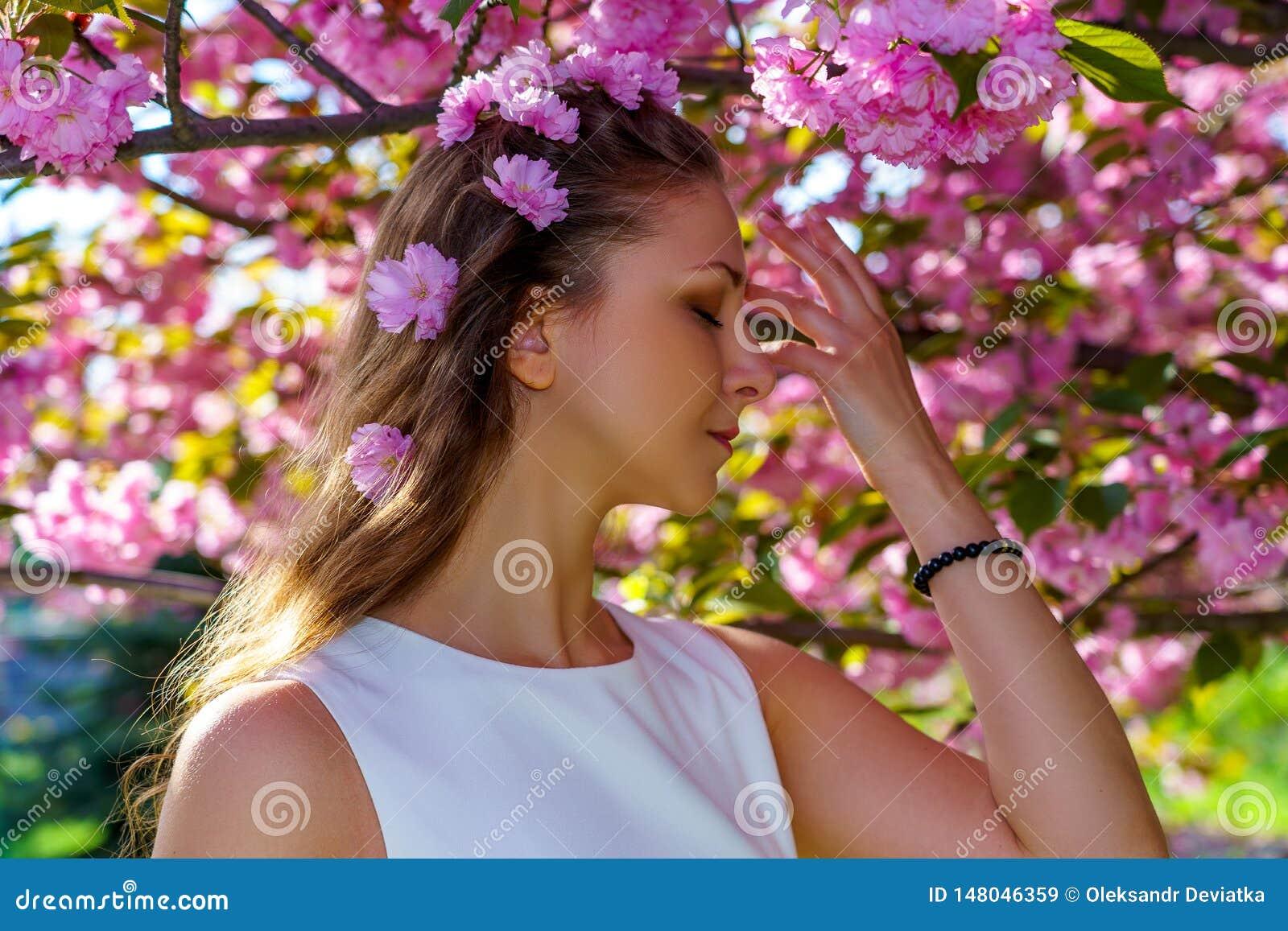 Le portrait haut étroit de la jeune belle femme avec les fleurs roses dans ses cheveux est dans la robe blanche pose l offre dans