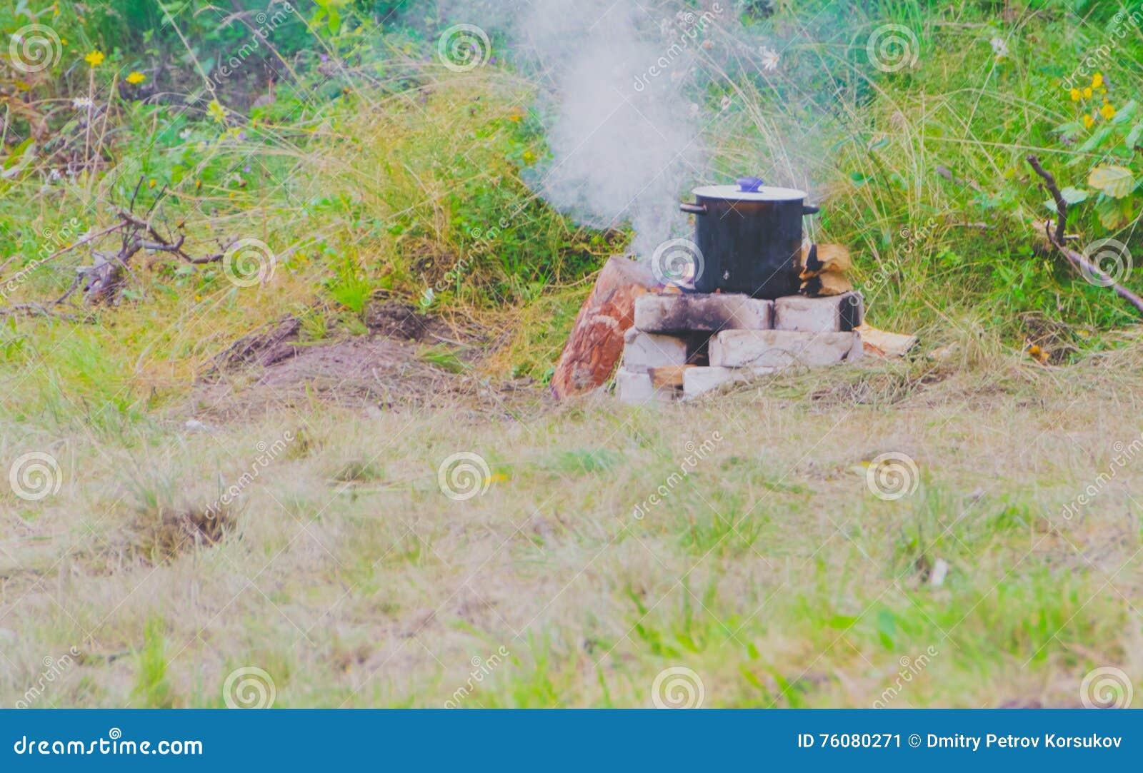 Le pot du repas est sur les roches et le feu